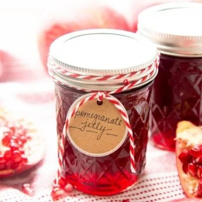 A gift tag tied with red and white string hangs from a jar of ruby red pomegranate jelly.
