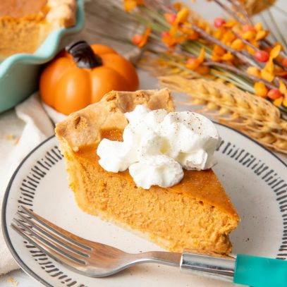 A single slice of pumpkin pie garnished with whipped cream sits on a plate with a teal-handled fork.