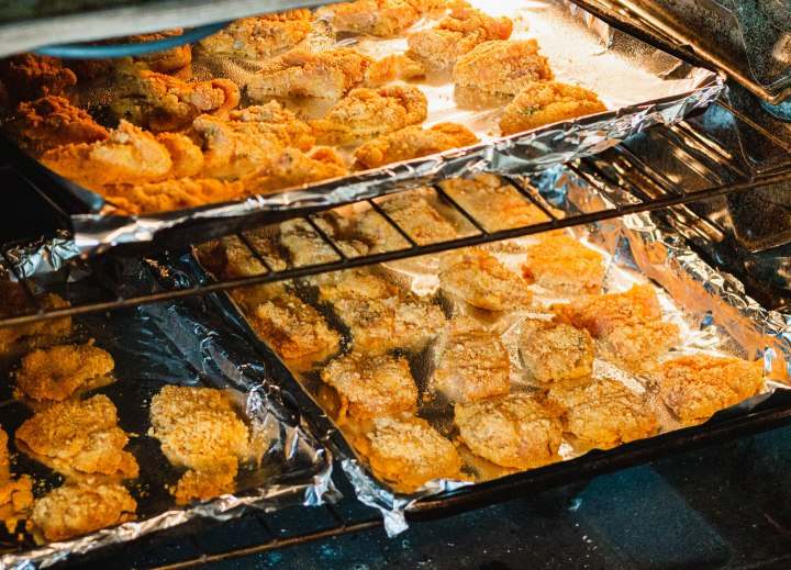 A full oven of nuggets. 3 trays filling top and bottom racks
