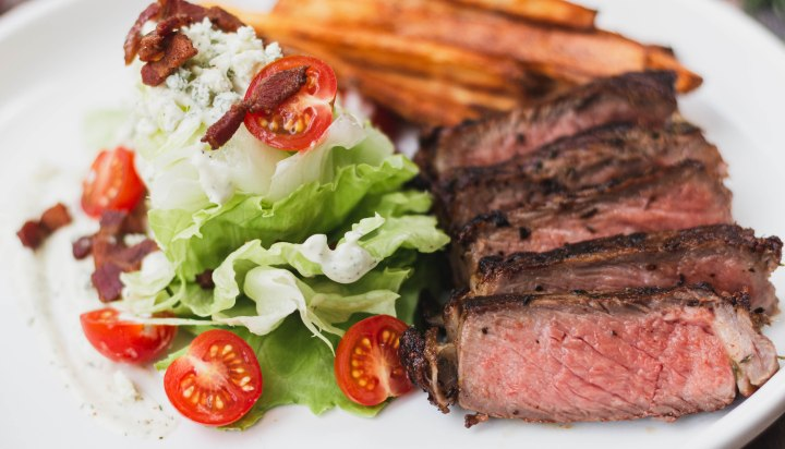Medium Rare NY Strip Steak served with a wedge salad and sweet potato fries