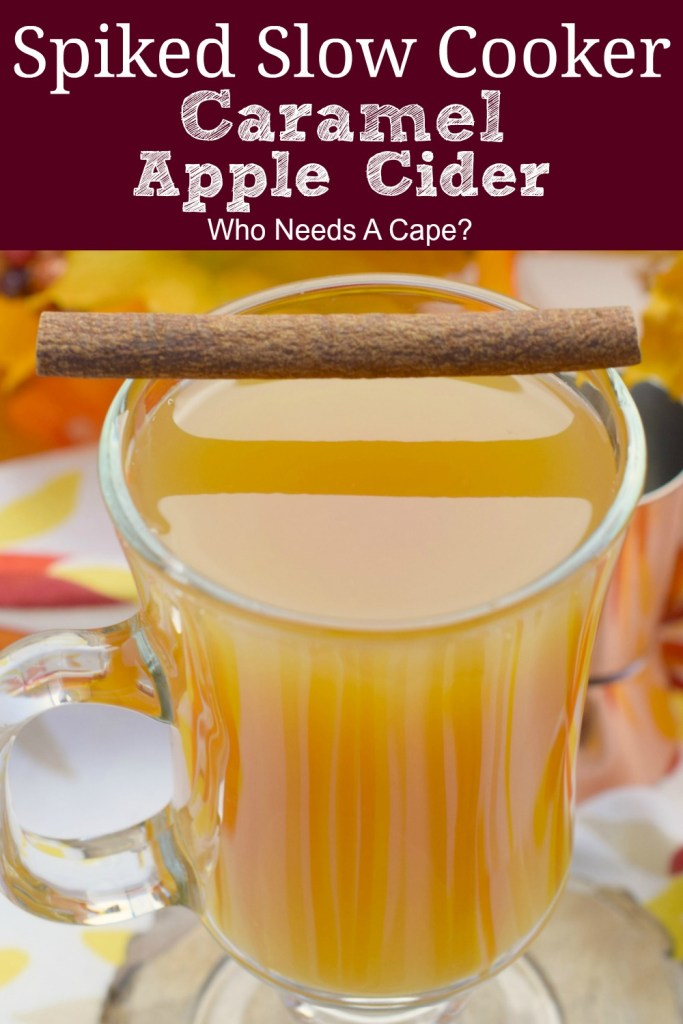 mug of spiked slow cooker caramel apple cider with cinnamon stick next to fall decor