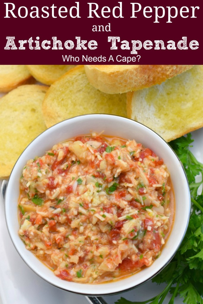 white bowl with silver rim holding roasted red pepper and artichoke tapenade next to fresh parsley and toasted baguette