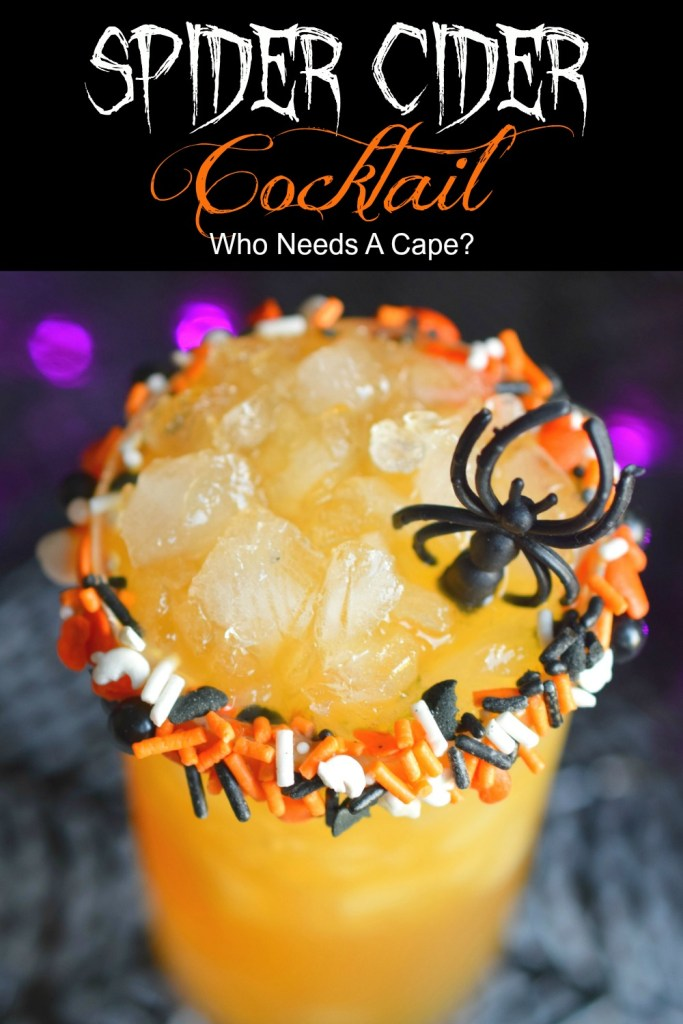glass with spider cider cocktail with ice in rimmed glass with Halloween sprinkles and spider cocktail stirrer
