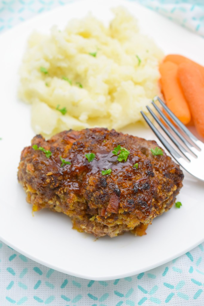 white plate on blue and white cloth with fork, carrots, mashed potatoes and mini meatloaf