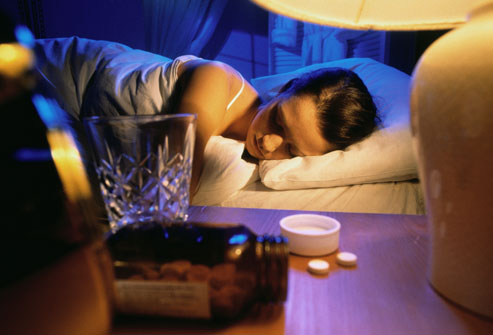 getty_rm_photo_of_woman_with_sleeping_pills_near_bed