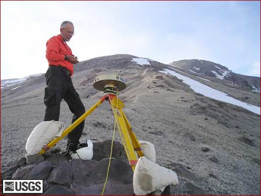 Man fiddles with machine mounted on tripod, mountain in background.