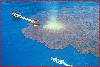 Brown oil on blue water, with a production platform in the center, and a ship nearby.