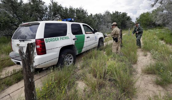 In this Sept. 5, 2014 photo, a U.S. Customs and Border Protection Air and Marine agents and U.S. Customs and Border Protection agents compare notes as they patrol near the Texas-Mexico border, near McAllen, Texas.