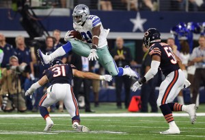 Sep 25, 2016; Arlington, TX, USA;  Dallas Cowboys running back Ezekiel Elliott (21) leaps over Chicago Bears safety Chris Prosinski (31) in the fourth quarter at AT&T Stadium. Mandatory Credit: Matthew Emmons-USA TODAY Sports