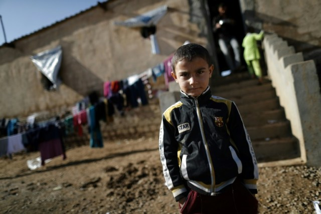 A displaced Iraqi boy, who fled the violence in the Iraqi northern city of Mosul as a result of a planned operation to retake the city from jihadists, poses at Hasan Sham refugee camp on Dec. 3, 2016. (Photo: Thomas Coex, AFP/Getty Images