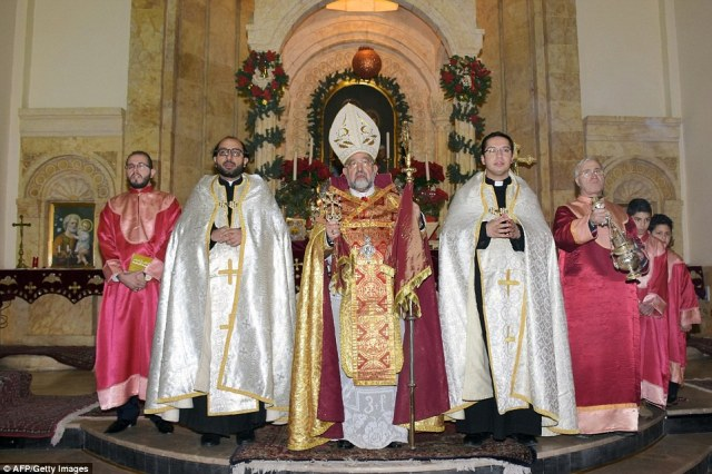 Christian clerics lead a mass at the Saint Elias Cathedral in Aleppo's Old City, which has been retaken by Syria's Army