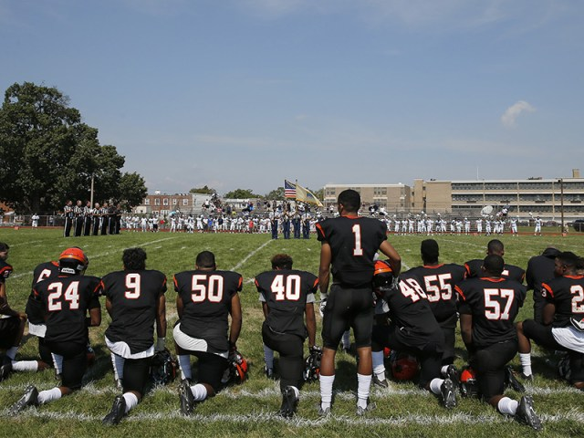 Woodrow Wilson High's Edwin Lopez (#1) stands while most of his teammates and coaches kneel during the national anthem before their game against Highland High School on September 10, 2016, in Camden, NJ. Photo courtesy of Yong Kim/Philly.com