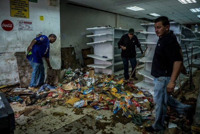 Employees worked on Friday to clean a supermarket that was one of the stores looted overnight in the El Valle neighborhood in Caracas, the Venezuelan capital. (Meridith Kohut for The New York Times)