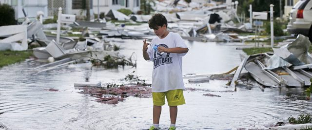 Gabriel Melendez, 9, washes his finger after cutting it on glass, while helping his grandmother clear debris from her destroyed home in the Naples Estates mobile home park in the aftermath of Hurricane Irma in Naples, Fla., Monday, Sept. 11, 2017. (AP Photo/Gerald Herbert)