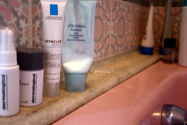 Skincare Products on the bathroom counter - How to Create a Travel Skincare Routine for Long Term Travel