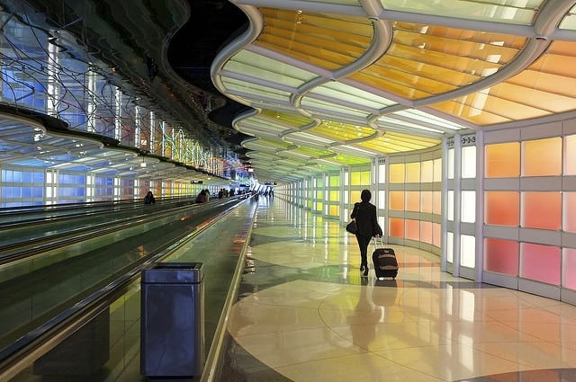 The Colorful Interior of an Airport with a Woman Walking Alone with her Bag - How to Survive a Long Flight