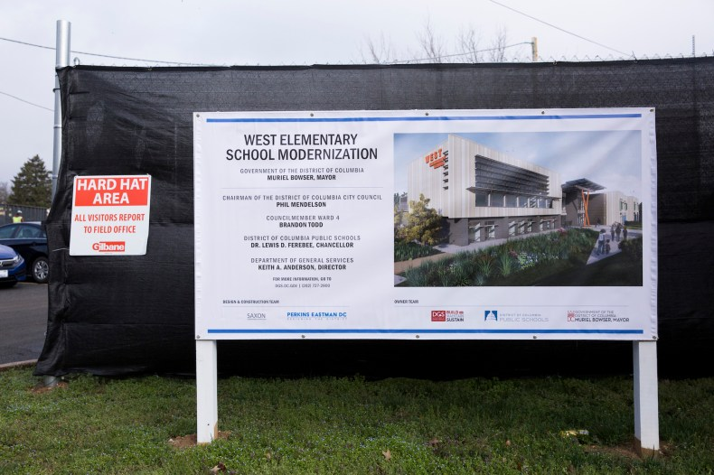 A projected image of the modernized West Elementary is shown outside of the school's construction area