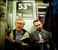Men watching a smart phone on the train