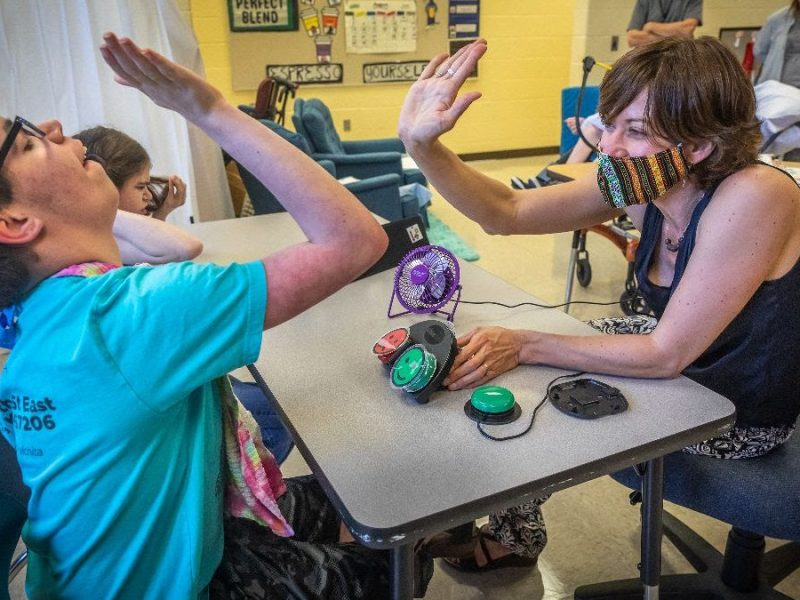 Wichita Public Schools speech pathologist Jennifer Owen, who specializes in augmentative and alternative communications, high-fives Bryan Stoner after completing a communications exercise at Northeast Magnet on Aug. 25.