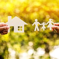 image of hands holding paper cutout of house and family