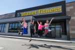 Teens leaping in the air in front of a Planet Fitness location