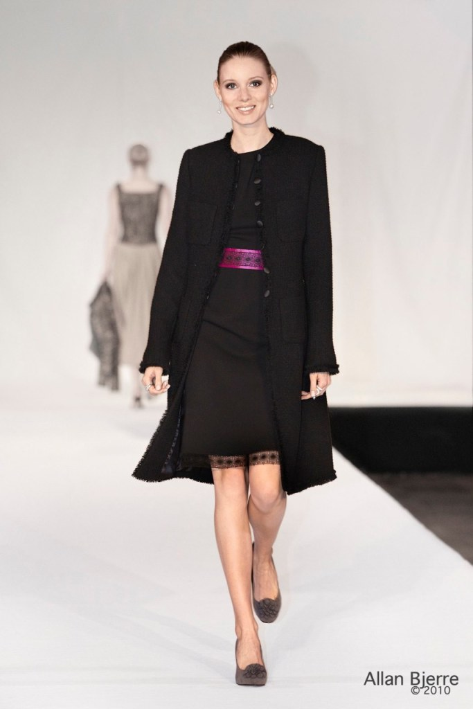 Sort kjole med blondekanter og bælte dertil lang bouclefrakke med lommer og frynser