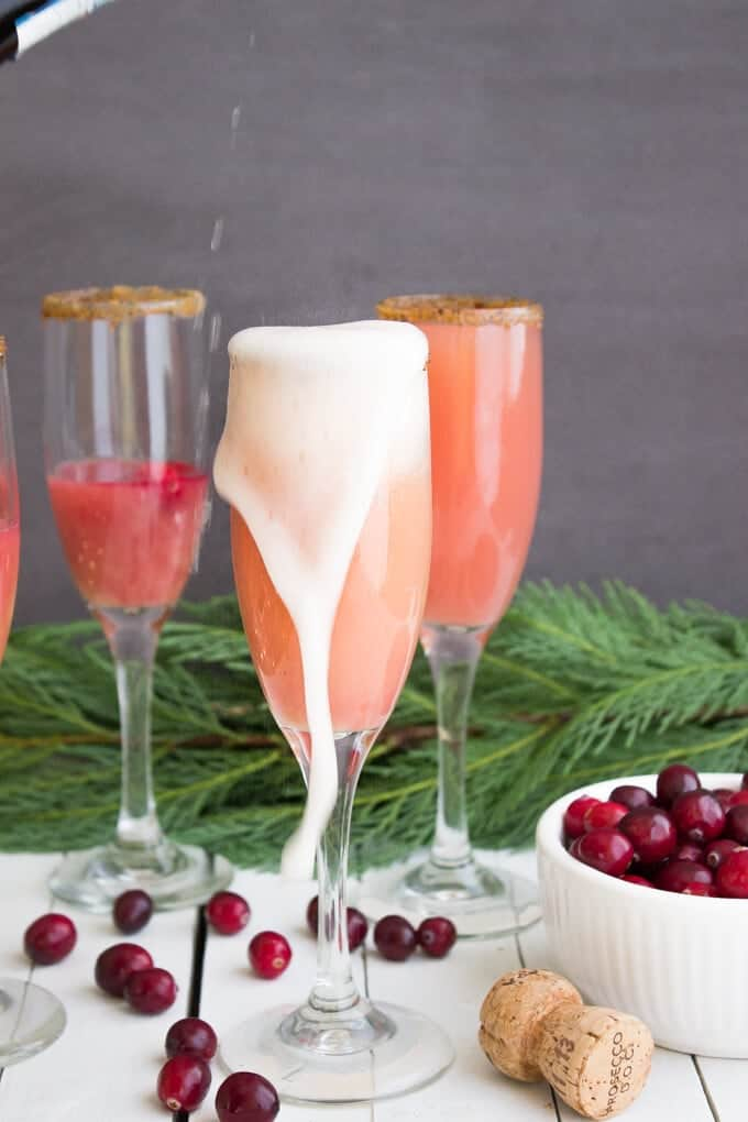 Cranberry Orange Mimosa - Fresh orange juice, cranberry juice, bubbly prosecco, and fresh cranberries with a vanilla sugar rim