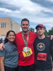 Two pacers and a runner, the author of this race report, stand at the finish line of the Burning River 100.