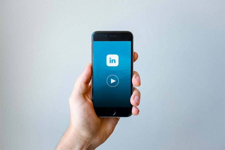 a hand holding a cellphone with linkedin and a video play icon