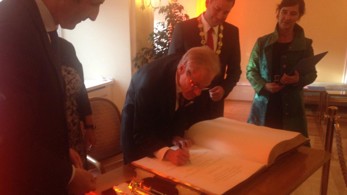 Professor Ekkehard Genth trägt sich in das Buch der Stadt Wiesbaden ein. Bild: Stadt Wiesbaden