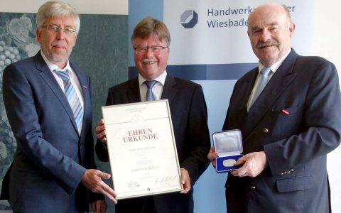 Hauptgeschäftsführer Bernhard Mundschenk und Kammerpräsident Klaus Repp übrreichen Arno Goßmann die Ehrenmedaille der Handwerkskammer Wiesbaden.