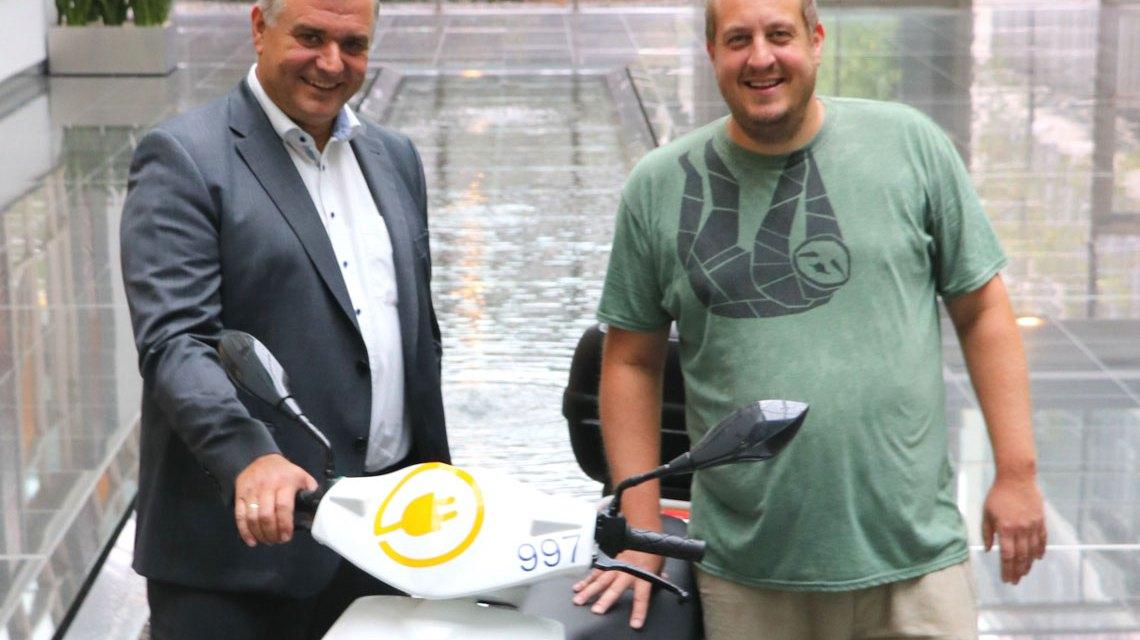 ESWE-Vorstandsmitglied Jörg Höhler (li.) und Teamleiter Michael Weinand vom Stadtjugendring bei der Roller-Übergabe im Atrium von ESWE Versorgun. ©2018 ESWE Versorgung