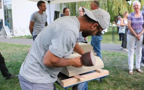 """Bei der Ausstellungseröffnung """"Skulpturen aus Stein"""" konnten nicht nur kreative Objekte aus Naturstein betrachtet werden: Ein Lehrling des Betriebes """"Naturstein Balz"""" brachte interessierten Besuchern das Steinmetz-Handwerk näher."""