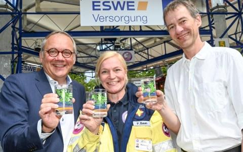 """Ralf Schodlok (l., Vorstandsvorsitzender der ESWE Versorgungs AG), Pia Baum (""""Seelsorge in Notfällen"""") und Designer Michael Spengler präsentieren auf der Rheingauer Weinwoche das Wasserglas 2019"""