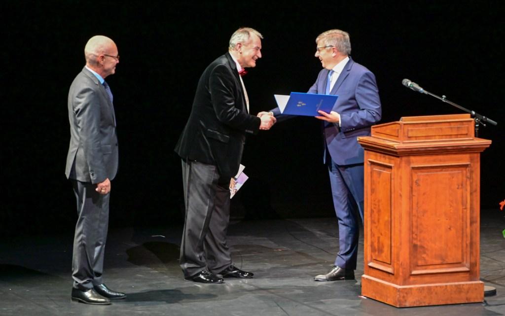 Gert-Uwe Mende übergibt die Urkunde zur Stadtplakette an Uwe-Eric Laufenberg.