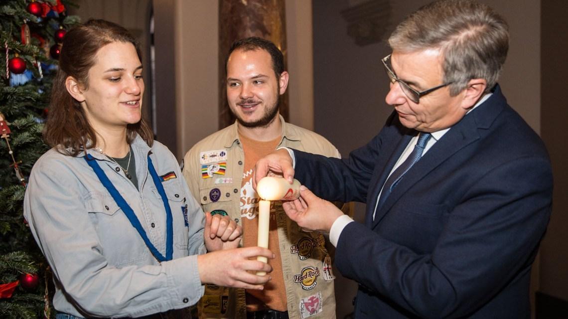 Oberbürgermeiszter Gert-Uswe Mende nimmt das Friedenslicht entgegen.