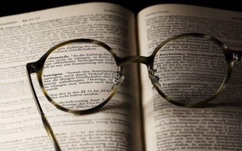 aufgeschlagenes Buch mit Brille, die Buchstaben verdeutlich. Literarische Mittagspause