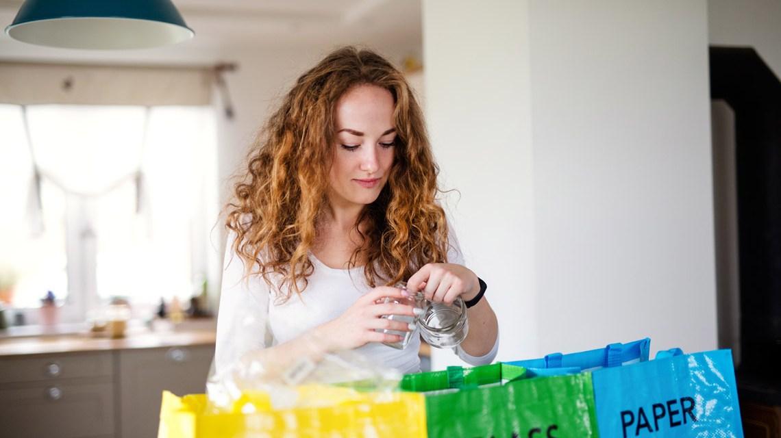 Umweltschutz: Frau steht in der Küche vor einem Fenster und sortiert Abfall.