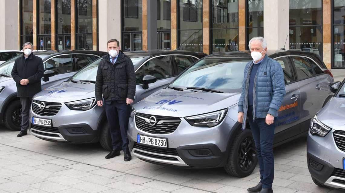Gert-Uwe mende, Jens Hasselbächer und Leo Kutscheid vor Autos des Fahrservices. Foto: R+V Versicherung