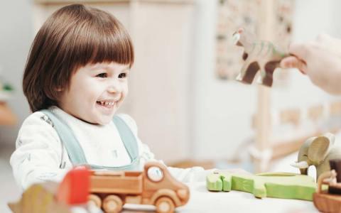 Tagesmüttervermittlung: Kind wird bespielt und lacht