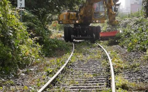 Bagger auf Schienen röäumt entlang der Aartalbahn auf.