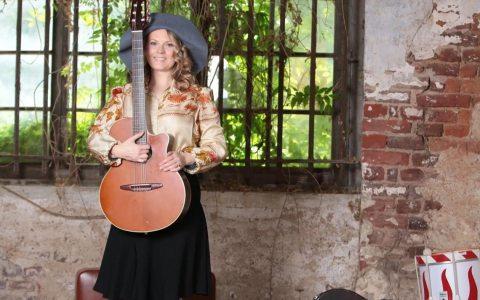 Patricia Kelly mit Gitarre in der Hand on Tour.