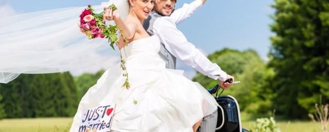 Frau mit Hochzeitskleid und Mann mit Hut fahren mit einer Vespa