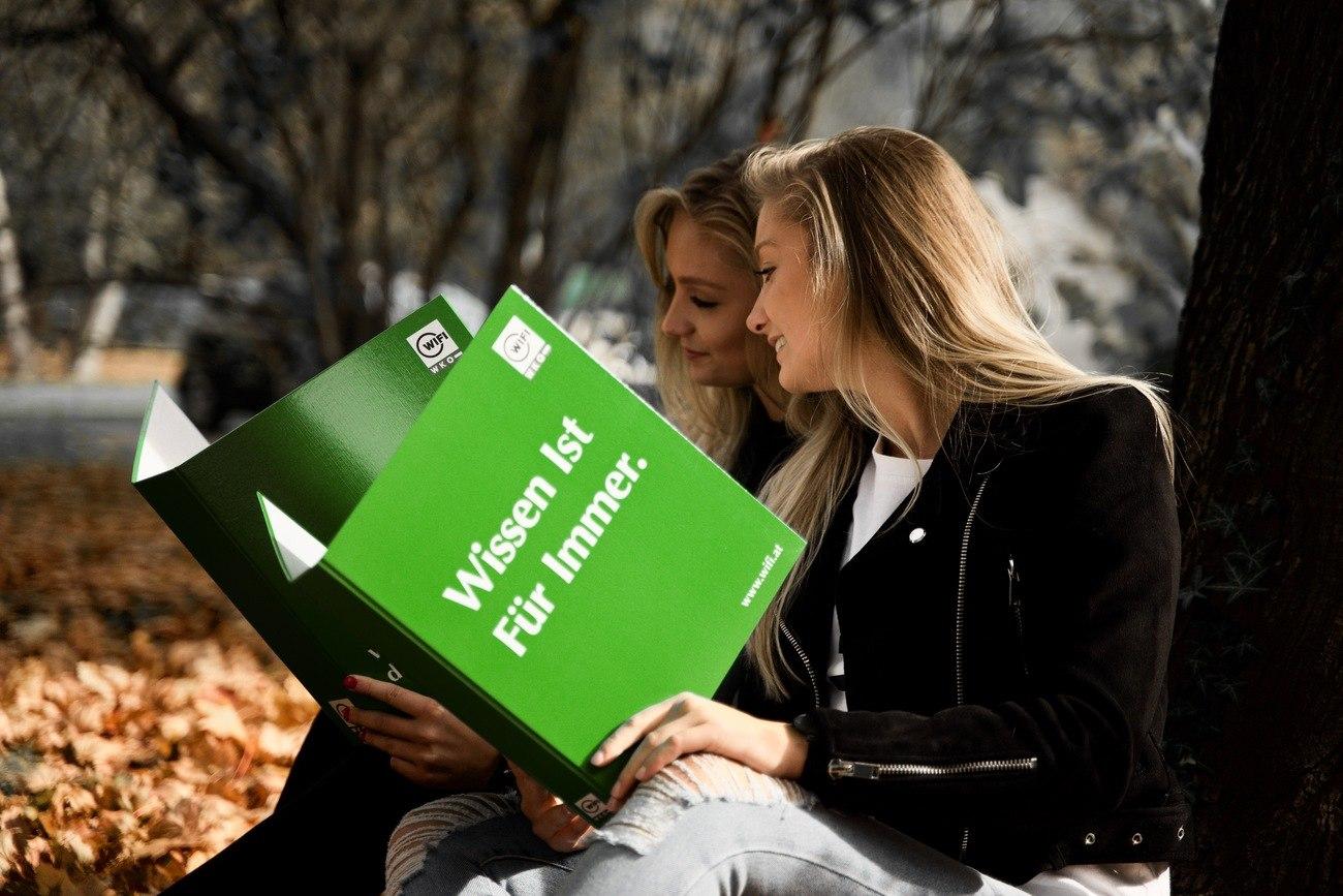 Zwei junge Frauen unter einem Baum mit einem WIFI-Kursbuch in der Hand lernen für die Berufsmatura.