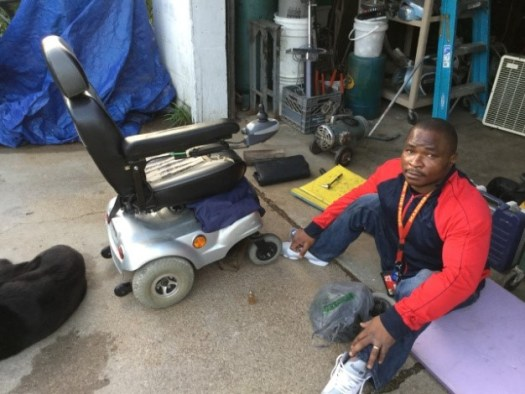 Koko brings his mobility device over to be repaired and adjusted.