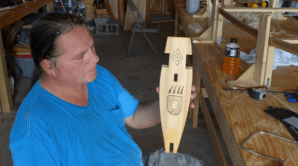 """Wayne showing one of the canoe's two inini-bagoog, decorated with a bear paw symbol. The shape of the finished piece explains the name """"manboard"""" (Photo Credit: Colin Connors)"""
