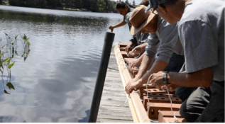 Wayne and his crew securely tie the cedar pieces to a set of bricks so that they can be submerged in a lake alongside a dock near Wayne's home (Photo Credit: Thomas A. DuBois)