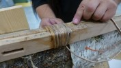 Lashing the gunwales with spruce roots (Photo credit - Colin Connors)