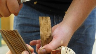 Trimming the laminated outwales with a crooked knife (Photo credit: Colin Connors).