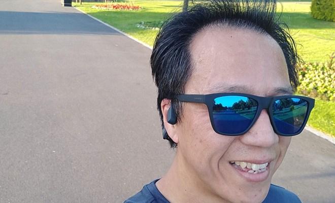Running through park wearhing Aftershokz Aeropex and sunglasses